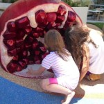 Children playing at the giant pomegranate
