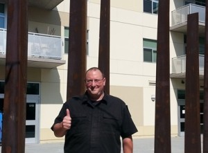 Sergeant Dueker gives the thumbs up in front of the 12 Tribes Sculpture at the Oshman Family JCC.