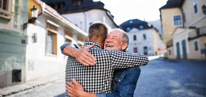 An adult hipster son and his happy senior father in town, hugging.